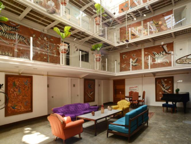 Lapa de várias tribos. Hotel Le Chateau da Lapa, ambiente no térreo com sofás coloridos, um piano ao fundo. No vão no meio do prédio de 3 andares
