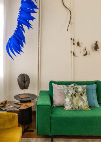 Atelier Botânico - loja carioca reabre com mostra de plantas e a participação de dez paisagistas e floristas. Sofá verde e um arranjo de penas azuis ao lado pendurado