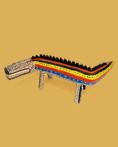 Calango em madeira, pintado com listras coloridas, feitas por artistas brasileiros