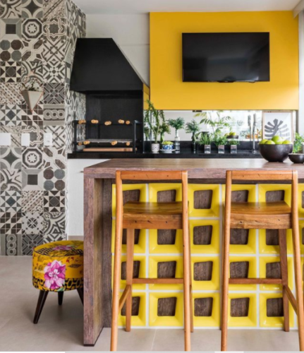 Varanda com churrasqueira. Decorada com uma parede de azulejo hidráulico estampado na cor cinza, balcão com elementos vazados na cor amarela e painel da tv também amarelo