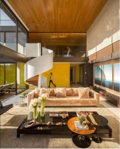 O poder das cores nos ambientes. Sala com o pé direito alto, janelas do piso ao teto que é revestido em ripas de madeira, a parede de fundo pintada de amarelo