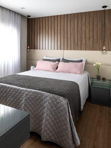 Quarto decorado em tons suaves, cabeceira em tecido bege a parede atrás em madeira ripada