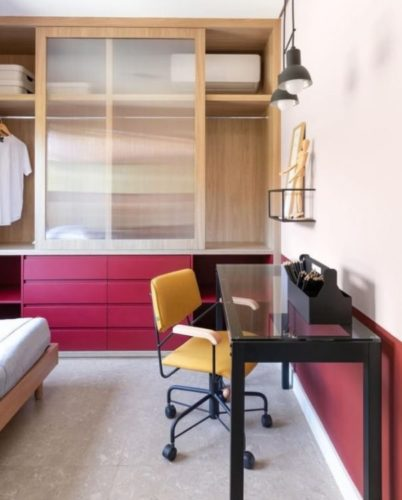 Armários com a parte de baixo, com gavetas na cor roxa e uma fixa pintada da mesma cor em volta do quarto
