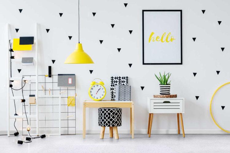 5 benefícios do piso vinílico, uma delas , conforto acústico. Parede branca com adesivos salpicados, em forma de triângulos na cor preta