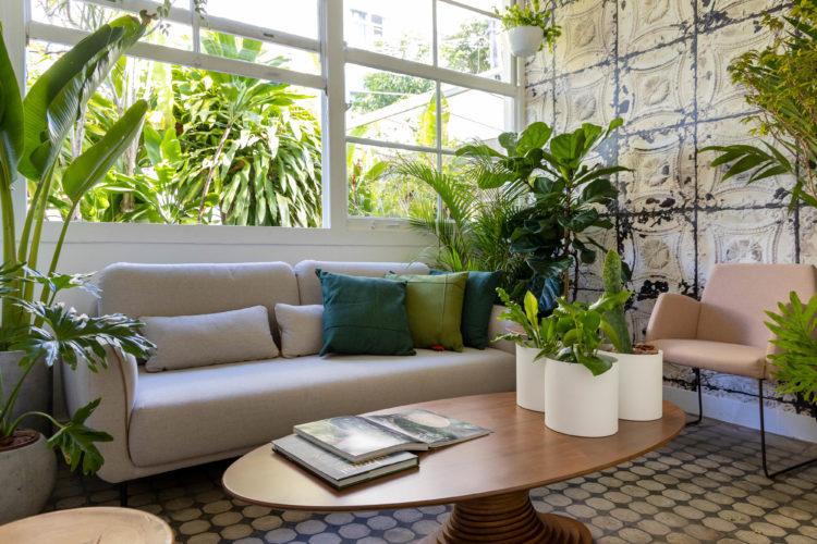 Loja do design Fernando Jaeger com mostra de paisagistas e floristas, sala com um sofá bege e mesa de centro oval em madeira com a assinatura do designer, varias plantas espalhadas pelo ambiente