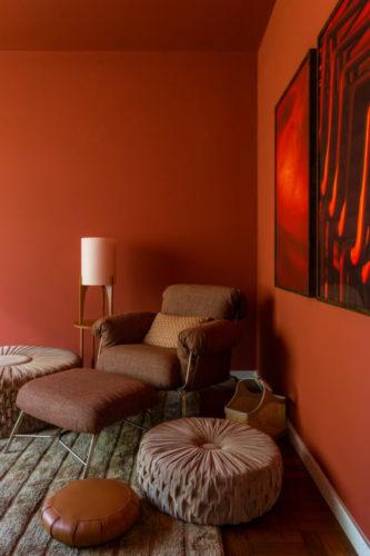 Canto da sala com as paredes pintadas de ocre, uma poltrona ton sur ton e quadros vermelhos na parede