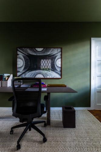 Escritório com a parede e o teto pintado de verde, mesa e cadeiras pretas