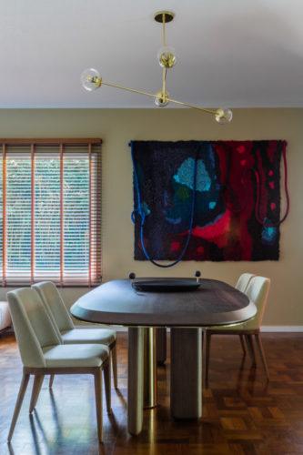 Sala de jantar decorada com uma tapeçaria na parede