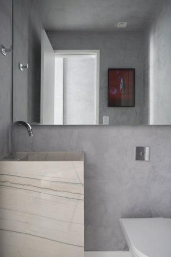 Apartamento compacto - 36m2 muito charmoso conseguiu ter espaço para o lavabo, que tem uma faixa de espelho em na metade de cima da parede e o restante em uma pintura imitando cimento.