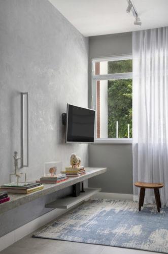 Apartamento compacto - 36m2 muito charmoso em Ipanema, Paredes cinzas , tv na parede e uma cortina de voal branco na janela.