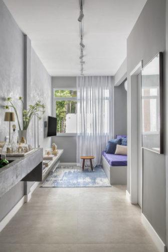 Apartamento compacto - 36m2 muito charmoso. Paredes na cor cinza imitando cimento, ao fundo na lateral espaço para um sofá que funciona como cama de hóspedes.