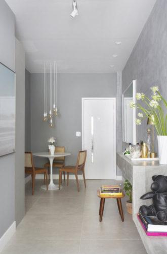 Apartamento pequeno e bem resolvido em Ipanema. Sala estreita com piso em porcelanato claro, paredes na cor cinza imitando cimento
