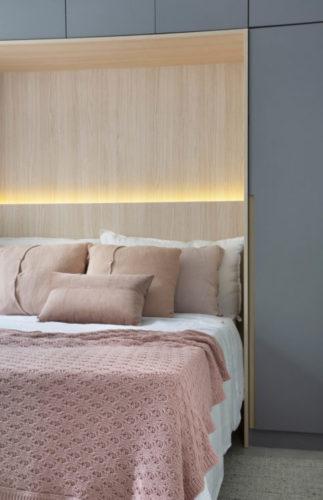 Cama entre armário. Parede de fundo da cama e teto, revestido em madeira. Armários superiores a na lateral, com portas cinza