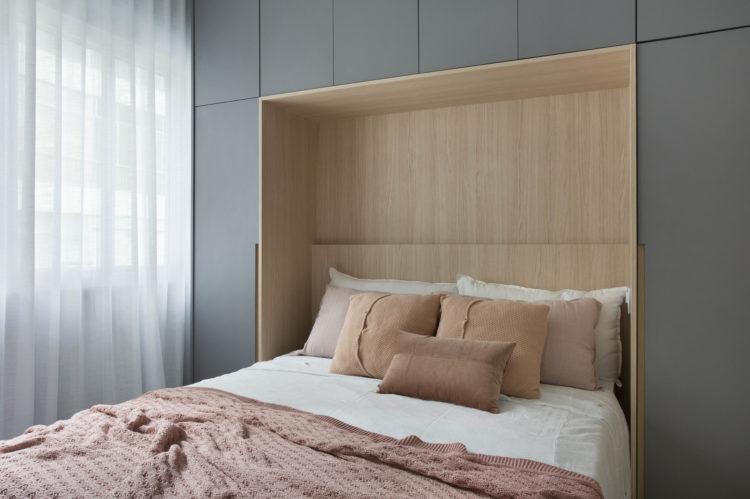 Apartamento compacto - 36m2 muito charmoso, A cama embutida no armário. Parede de fundo do armario revestida em folhas de madeira. Roupa de cama rosa e branca, e as portas dos armários nas laterais e em cima na cor cinza