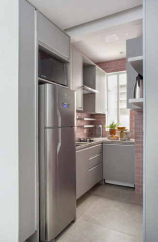 Cozinha pequenas com as paredes revestidas de azulejo retangular na cor rosa, armários na cor cinza e geladeira cromada.