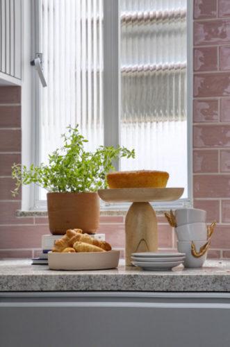 Vaso de barro com planta, um bolo em uma parto de bolo em madeira e xicaras brancas com assas douradas
