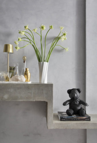 Parede cinza, uma vaso de flor branco com poucas flores, uma bandeja arrumada para bar em cima de uma aparador em concreto e enfeitando um urso preto.
