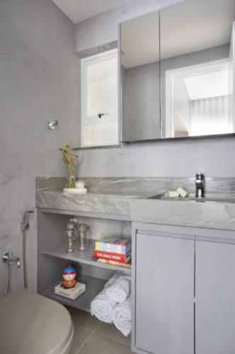 Banheiro todo na cor cinza, paredes pintados imitando cimento, bancada com material sintético também na cor cinza, armários idem, Em cima da bancada um pequeno armário com portas em espelho e uma janela ao lado com esquadria branca