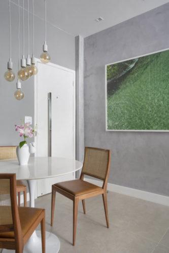 Sala pequena decorada com paredes pintadas imitando cimento, porta de entrada branca, mesa de jantar branca com tampo redondo em mármore, varias luminárias pendentes com um fio branco e lâmpadas de filamento, cadeiras em madeira