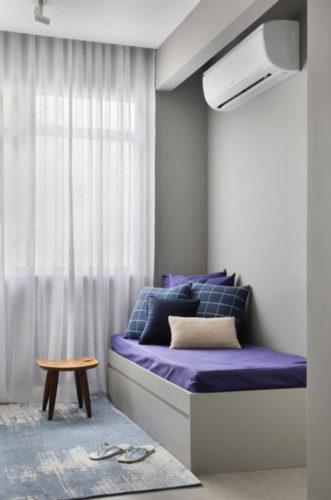Sala com paredes pitadas na cor cinza, colchão em cima de tablado de madeira também na cor cinza , e com o colchão revestido com uma capa na cor azul