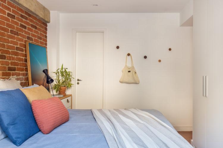 Quarto de casal com parede em tijolinho e armário branco