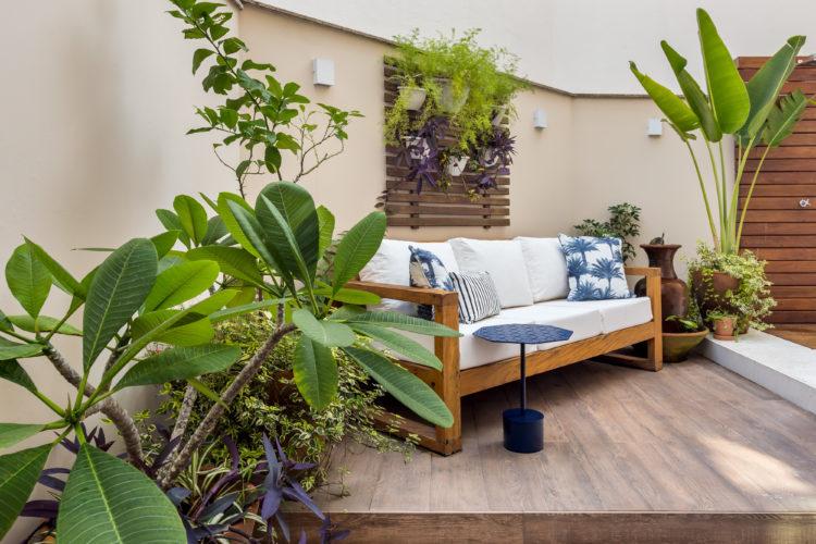 Apartamento térreo com ares de casa. Área externa com sofá em madeira e estofados brancos, almofadas com estampa de coqueiros azuis, e ao lado, vasos de plantas.