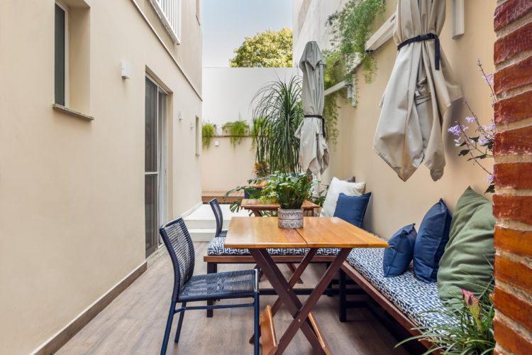 Apartamento térreo com ares de casa, na lateral , um corredor com mesa e banco em madeira, ombrelones na parede e um banco com almofadas azuis enconstado