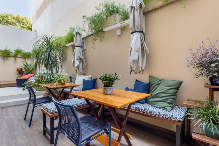 Apartamento térreo com ares de casa. Na parte externa, banco enconstado ao longo da parede, com almofadas estampadas nas cores azul e branco. Mesa quadrada em madeira, cadeiras azuis e na parede, instalado dois ombrelones articuláveis.