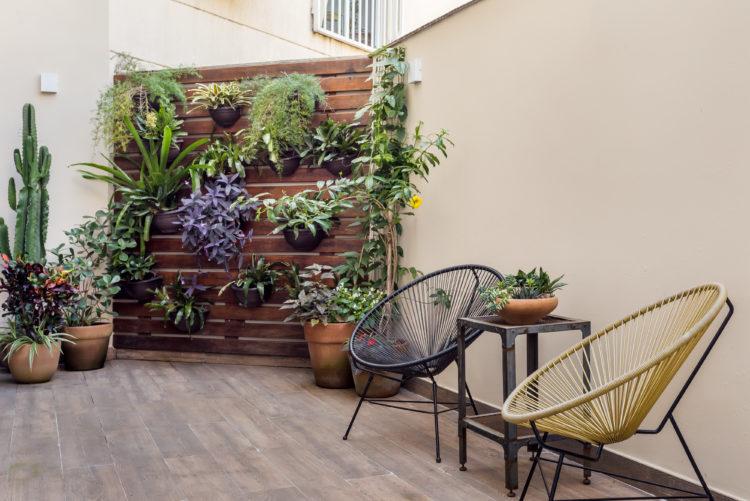 Área externa de um apartamento, com duas cadeiras e uma divisória em ripado de madeira ao lado, repleto de plantas
