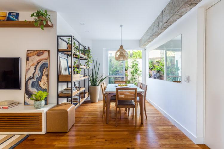 Sala de jantar com piso em madeira e porta para área externa.