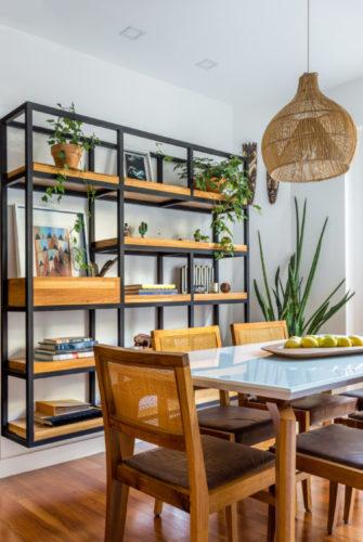 Sala de jantar com mesa e cadeiras em madeira, luminária pendente em palha e na parede, uma estante suspensa em ferro e madeira com objetos para enfeitar, como livros e plantas