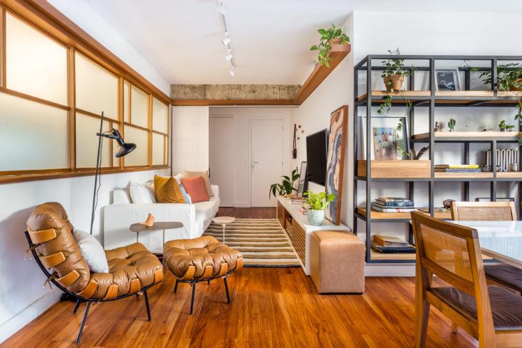 Sala com piso em madeira corrida, planta em formato de L. Na parte mais estreita, sofá branco na parede, tack em madeira em frete e tv na parede. Ao lado, cadeira em couro e madeira com puff