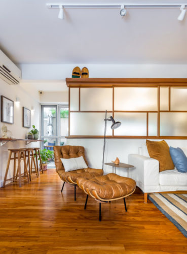 Sala com piso em madeira, poltrona em couro e madeira