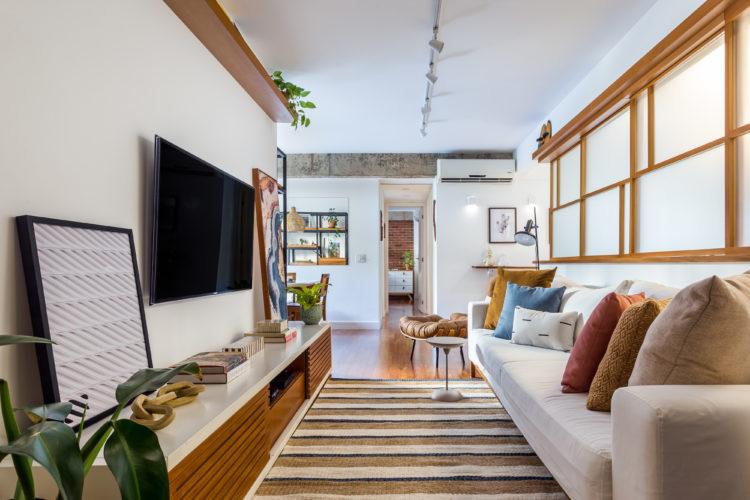 Sala de tv estreita, com rack baixo em madeira e lacca branca, tapete listrado, sofá branco com almofadas coloridas