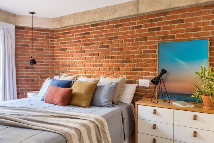 Quarto de casal com a parede ao fundo da cama em tijolinho