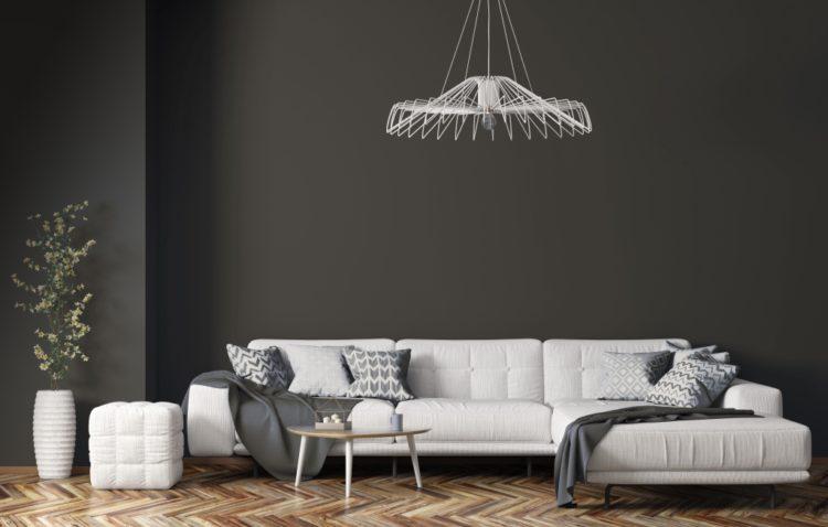 Parede de fundo pintada de cinza, e na frente um sofá branco. essa é a Cor do ano de 2021: Bronze Conectado da marca Sherwin Williams