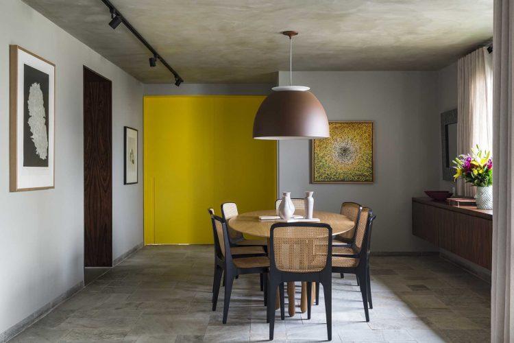 Porta de entrada modelo pivotante, pintada de amarelo.