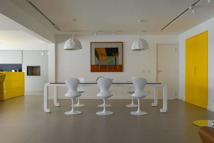 Sala bem ampla, com mesa de jantar em tampo de vidro e pés brancos, cadeiras brancas, porta de entrada dupla pintada de amarelo
