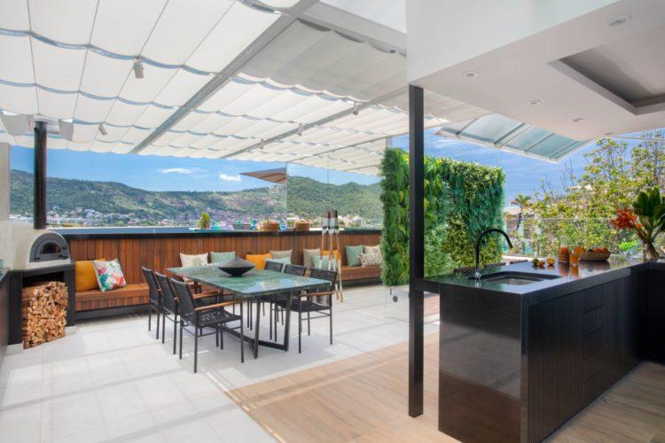 Cobertura com área externa, toldo, mesa quadrada, forno de pizza, piso em porcelanato claro misturado com porcelanato imitando madeira.