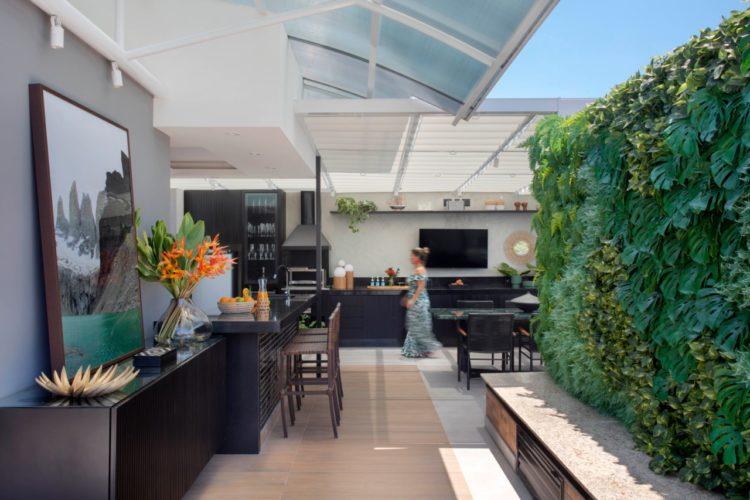 Dicas para acertar na escolha do piso externo. Cobertura com área externa e cozinha gourmet. Piso em porcelanato imitando madeira, parede verde ao lado