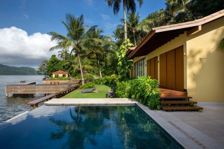 Dicas para a escolha do piso externo. Casa em Angra, piscina com borad infinita de frente para o mar , piso claro e antiderrapante ao lado, casa pintada de amarelo