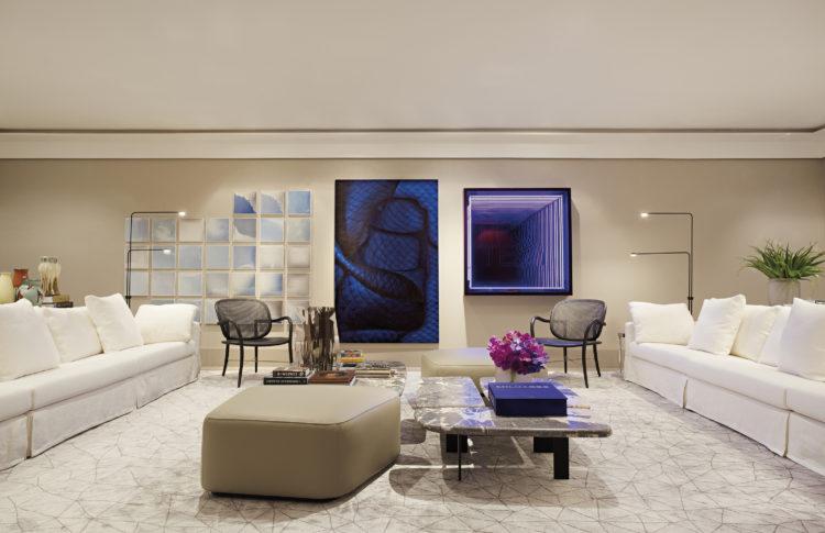 Sala com dois grandes sofás brancos, um em frente ao outro, no meio mesas de centro em mármore com puff ao lado
