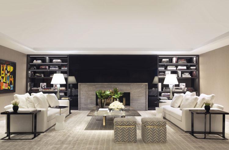 Sala com dois sofás brancos , um da frete no outro e ao fundo, parede pintada de preto com uma lareira no centro, em cada lado, estantes