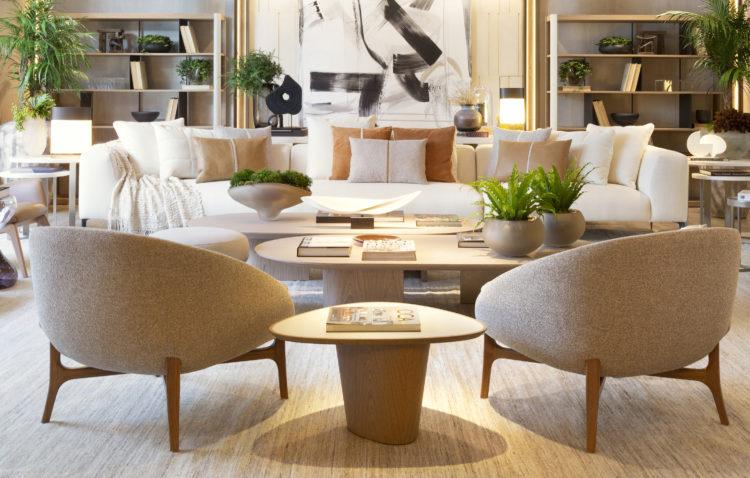 Artefacto Haddock Lobo apresenta Mostra 2021, espaço assinado pela arquiteta Debora Aguiar. Duas poltronas beges com pé em madeira e ao fundo, um sofá branco com muitas almofadas