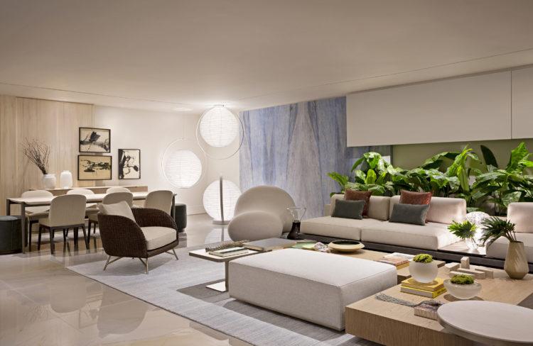 Ambiente de mostra de decoração, Sala ampla, sofá branco com plantas atrás e no fundo, 3 luminárias redondas de papel arroz