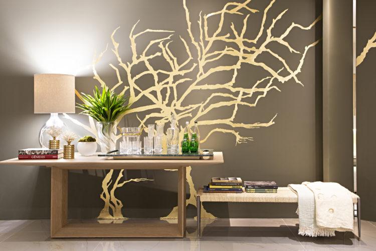 Artefacto Haddock Lobo apresenta Mostra 2021. Espaço decorado por Patrícia Penna. Móvel servindo como bar, parede atrás pinada de marrom com aplicação de adesivo com desenho de uma arvores com galhos sem flor