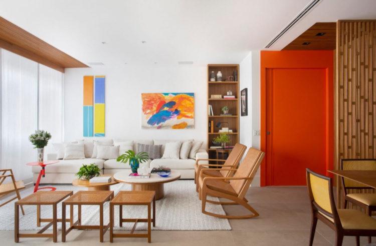 Sala clara, com sofá e almofadas brancas e peças de mobiliario em madeira. Porta de entrada e todo a aprefe pintada de laranja, efeito que camufla um pouco a porta