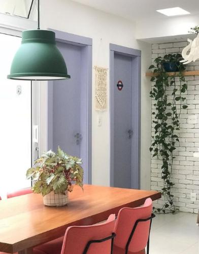 Parede de tijolinho branco, ao lado, duas portas pintadas na cor lavanda. Mesa de jantar em madeira e cadeiras rosas