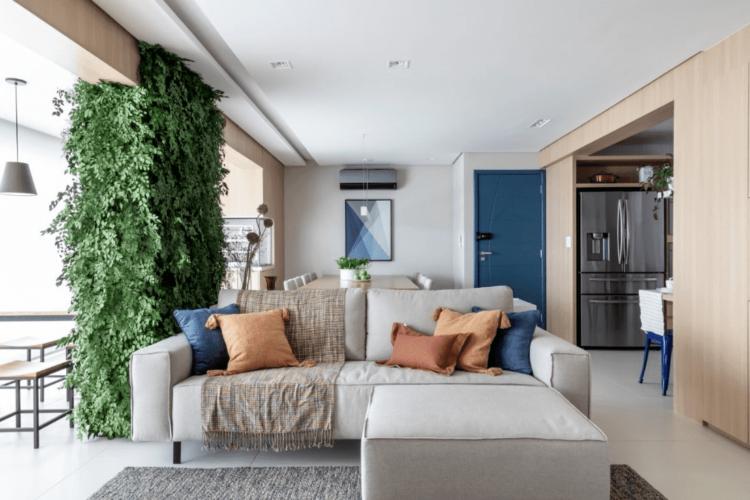 Portas coloridas – protagonistas da decoração. Sala ampla e clara, na frente sofá bege com alfadas lisas e ao fundo parede branca com a porta de entrada na cor azul. Coluna ao lado do sofá com jardim vertical