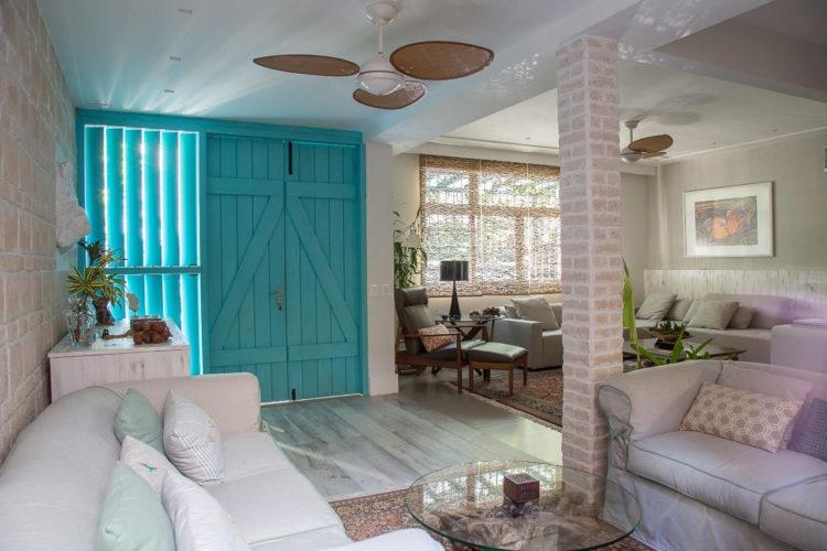 Modelo da porta de entrada, pintada de turquesa, lembra de um estabulo.